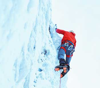 Climber in red jacket climbing an ice wall
